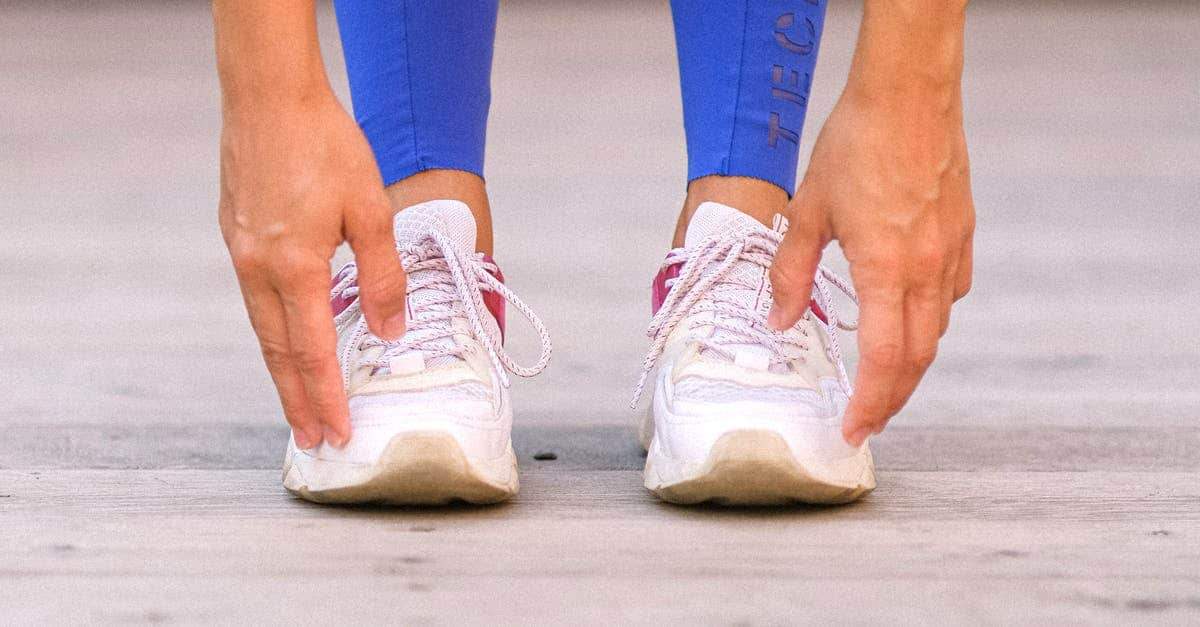 A close up of feet wearing blue and white shoes